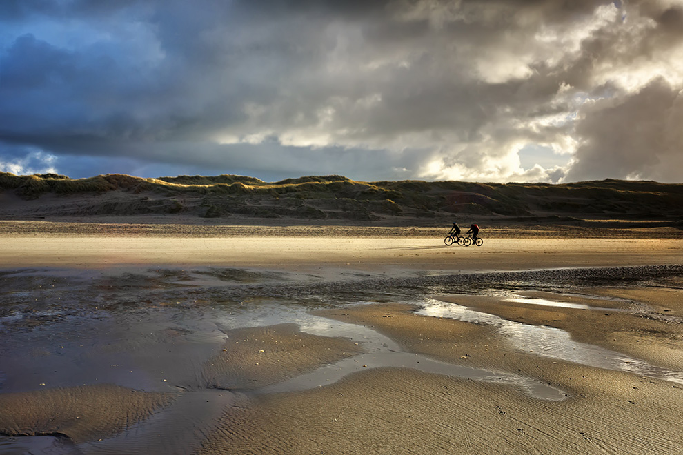 sport cyclists on north sea beach